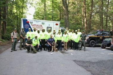 Forest Rangers and local emergency response pose for picture in front of ambulance