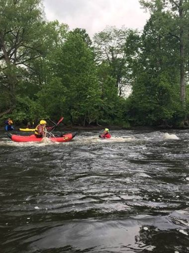 Forest Rangers and instructors paddling kayaks in water