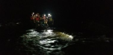 Dark photo of Forest Rangers helping hikers through water
