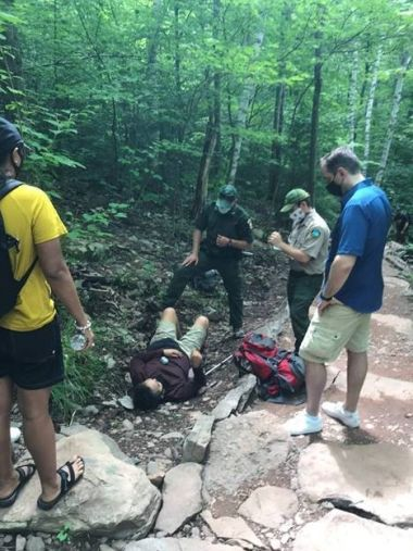 a male hiker lays on the side of the hiking trail on the ground while being evaluated by Forest Rangers