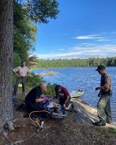 Forest Ranger and EMS help woman in stretcher on the edge of the lake