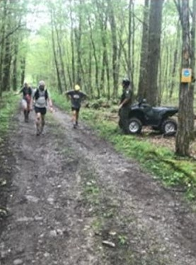 Three runners on a woodsy trail passing an ECO next to an ATV