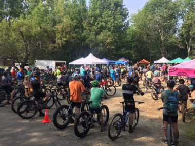 cyclists lined up for a race with tents in the background