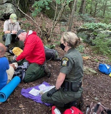Ranger kneeling while administering first aid to hiker in woods