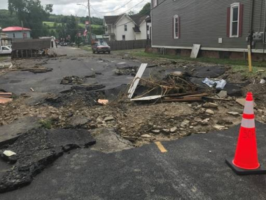 large break in pavement due to flood damage