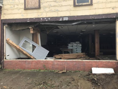 building with front window blown out due to flood damage