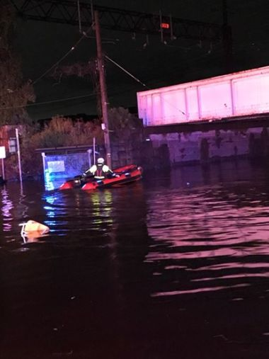 Rangers navigating flood waters at night in a raft