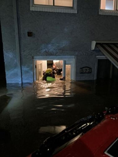 Rangers helping flood victims out the front door of a building, water is chest-high