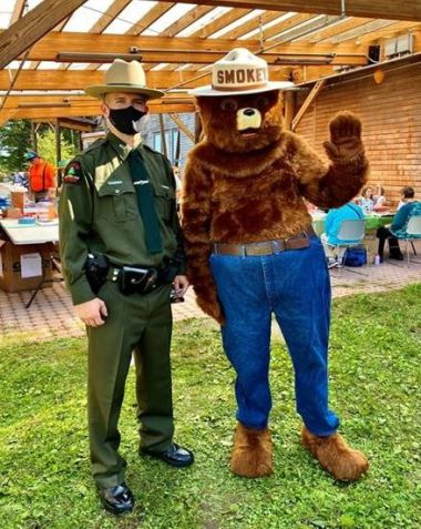 Smokey Bear and a Ranger pose for picture under a pergola