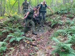 Rangers in the woods carrying hiker to safety on the trail