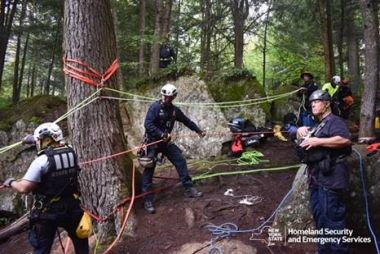 emergency response personnel perform rope training in the woods