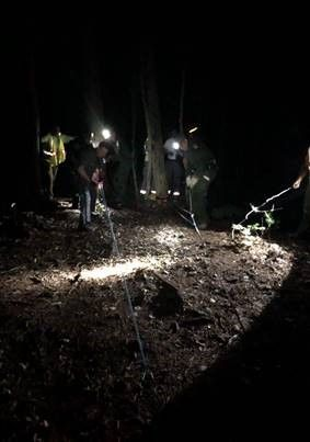 Forest Rangers in the dark woods with headlamps performing a rescue