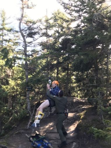 Ranger helps hiker as they're lifted out of the woods with a leg injury