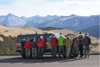Forest Rangers and volunteers pose for a group photo with mountain range in the background