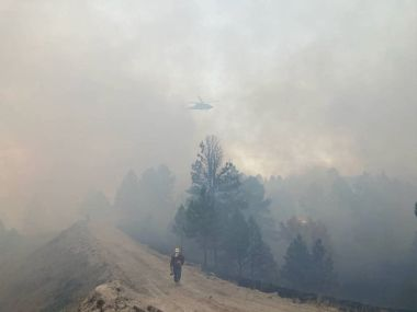 Smoky mountainous scene with a firefighter walking across the landscape