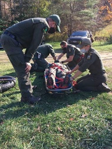 Forest Rangers participating in a training while loading a person onto a stretcher