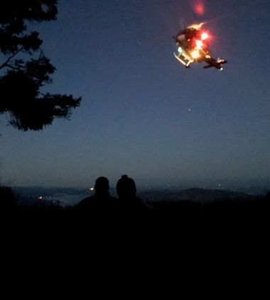 a helicopter in the dark night sky with lights on