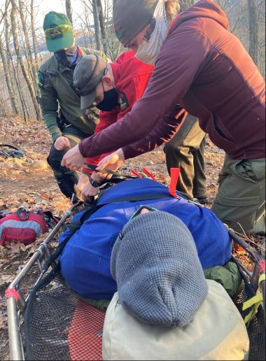 Forest Rangers splinting a hiker's leg in the woods