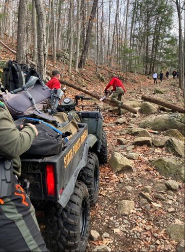 Forest Ranger clearing a path of a fallen tree as other forest rangers move up the trail with an ATV