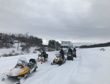 snowmobiles lined up to help with winter storm