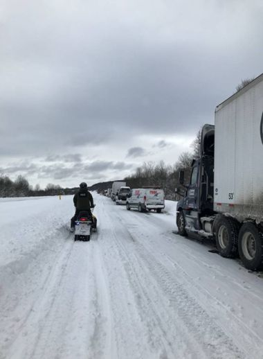 Forest Ranger rides along slow-moving traffic on a snowmobile