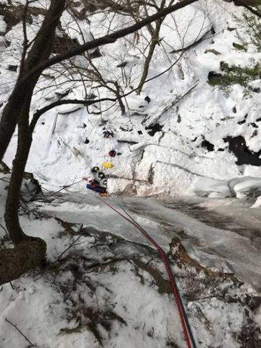 View looking down an icy ridge at Forest Rangers rescuing climber below