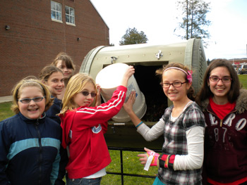 six female middle school students standing around a circular tall composter as one girl in a red jacket tips food scraps from a plastic bin into the opening of the composter.
