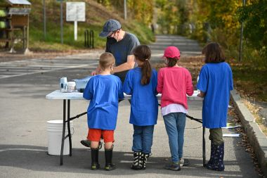 Children stand at table with adult testing water samples