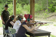 Young women practice shooting while overseen by an Environmental Conservation Officer