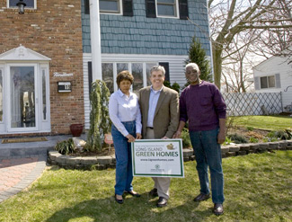 Three people standing in front of a house (the homeowners and the town supervisor) holding a Long Island Green Homes sign