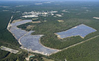 Aerial view of solar panels looking like small lakes among trees