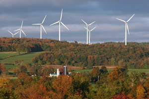 Several white wind turbines against a cloudy sky with trees, grass and farm in the foreground. Fall scene.