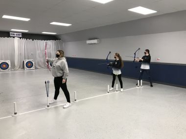 Female archers line up to aim their shots