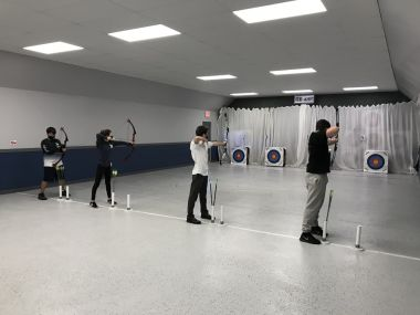 male archers line up and aim their shots