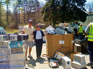 Two people are standing surrounded by boxes of electronic waste that has been dropped off for recycling