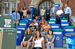 Students from a North Hempstead school sit on the entrance steps surrounded by blue and green recyling bins. Staff and the town supervisor stand behind on the top of the steps