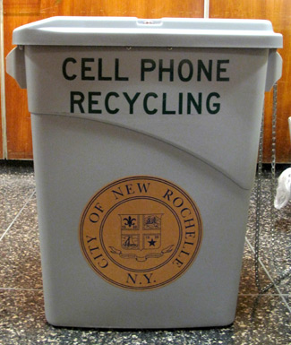 Close up picture of a tall grey bin with the words cell phone recycling and the city's logo on the front