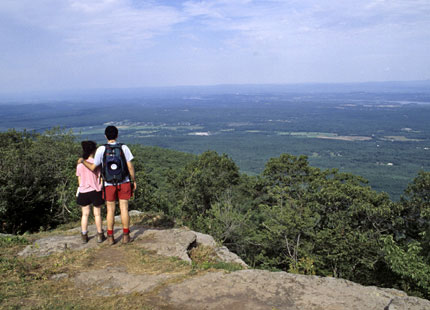 Two hikers enjoy the spectacular view of the Hudson River Valley and beyond from a rocky outcrop along the popular Escarpment Trail in the Catskill's North-South Lake campground.