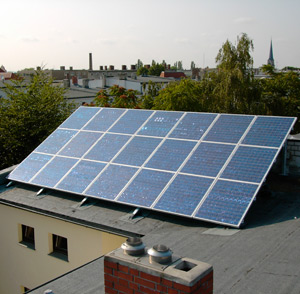 NYC skyline in background and flat roof building with solar panels on top in foreground