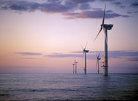 windmills in the ocean at sunset