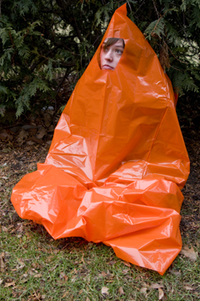 A person in an improvised shelter made from an orange trash bag with a hole for the face.