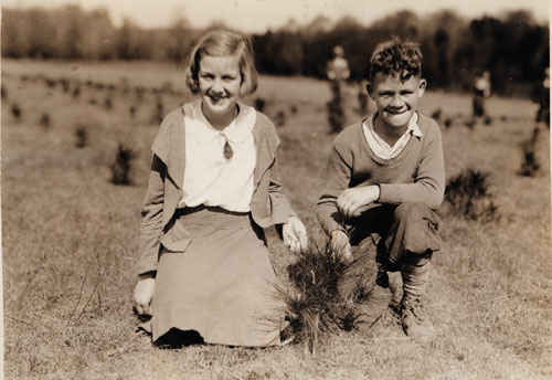 An old photgraph of a boy and a girl kneeling by a newly planted tree seedling