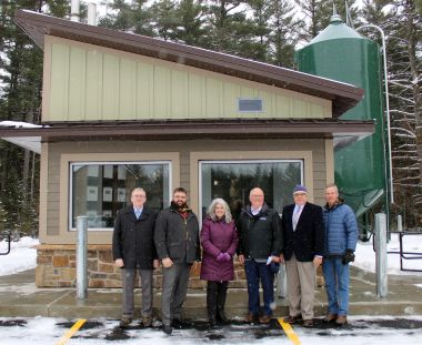 Six people standing in front of the building and its new heating system