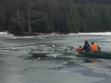 Two rangers in a canoe rescuing a man who broke through ice on a lake