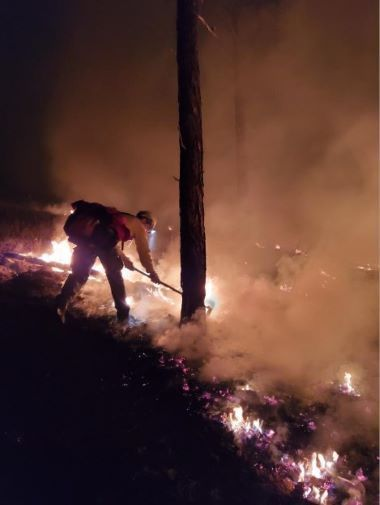 fire and smoke with a memeber of firefighting crew working to control wildfires