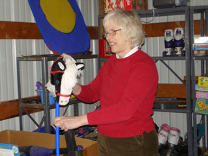 Lady in red sweater holding a hobby horse toy