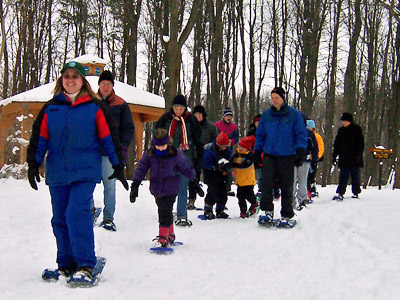 Adults and children snowshoeing at Reinstein Woods