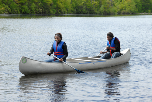 two young people paddling in canoe