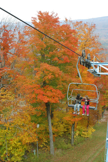 two kids riding a sky lift in autumn