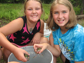 Two girls holding frogs